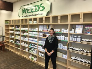 Rory standing in front of superfoods and supplements at Weeds. (Photo Credit: Weedsgg.ca)